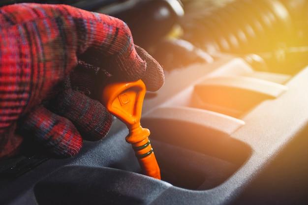 Mechanica hand houden peilstok oliepeilmeter met oranje kleur voor het controleren van het motoroliepeil van het motorsysteem, automotive onderhoudsconcept. Premium Foto