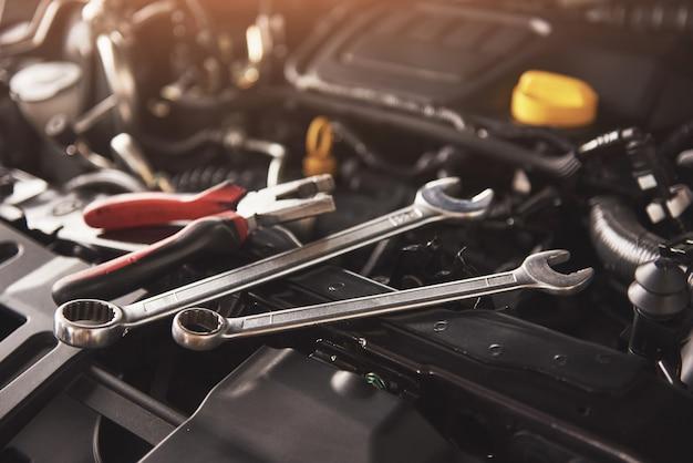 Mechanische hand controleren en repareren van een kapotte auto in de garage van de auto-service. Gratis Foto