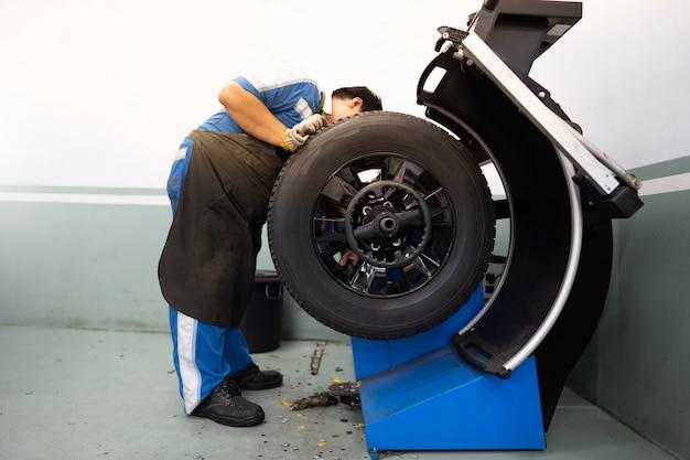 Mechanische mens die en reparatie werkt of banden met wielmachine in bandopslag controleert. Premium Foto
