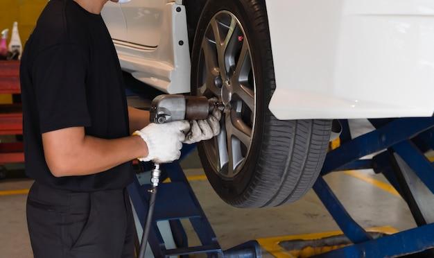Mechanische mens met het hulpmiddel veranderende banden van de effectmoersleutel van auto in auto autodienstwinkel Premium Foto