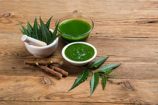 Medicinale neem bladeren in vijzel en stamper met neem pasta, sap en takjes op houten tafel Premium Foto