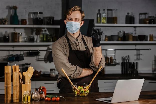 Medio geschoten chef-kok die met masker saladeingrediënten mengen dichtbij laptop Gratis Foto