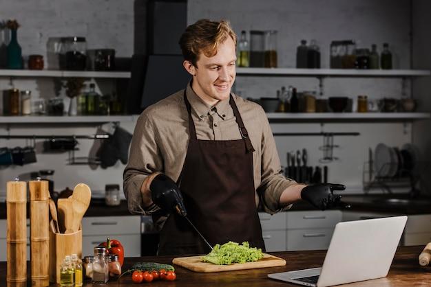Medio geschoten chef-kok die met salade laptop bekijkt Gratis Foto