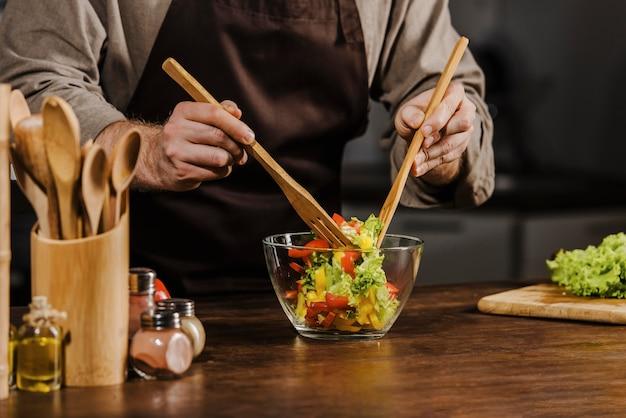 Medio geschoten chef-kok die saladeingrediënten mengt Gratis Foto