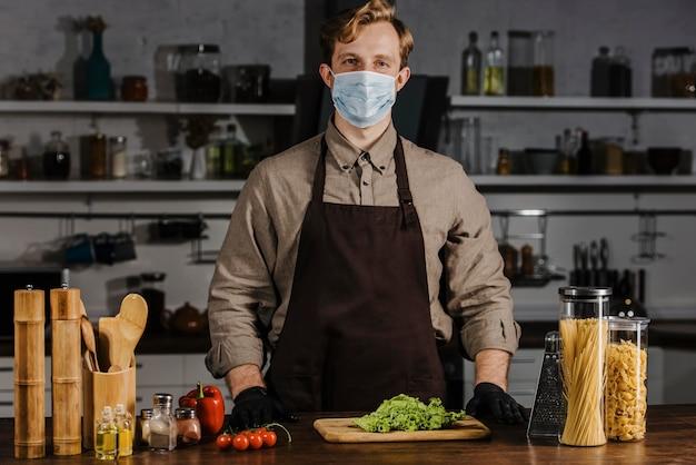 Medio geschoten chef-kok met masker en salade Gratis Foto