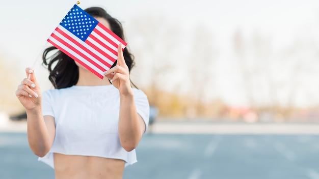 Medio geschotene vrouw die de vlag van de vs over gezicht houdt Gratis Foto