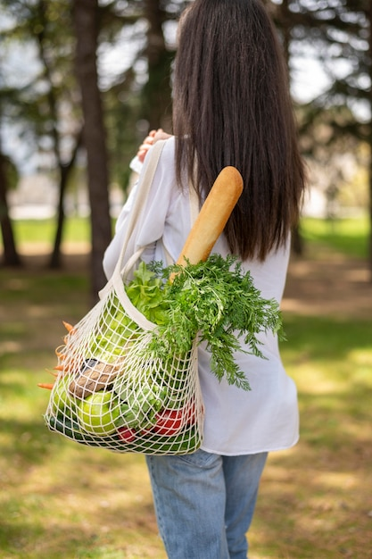 Medio geschotene vrouw die herbruikbare zak buiten houdt Gratis Foto