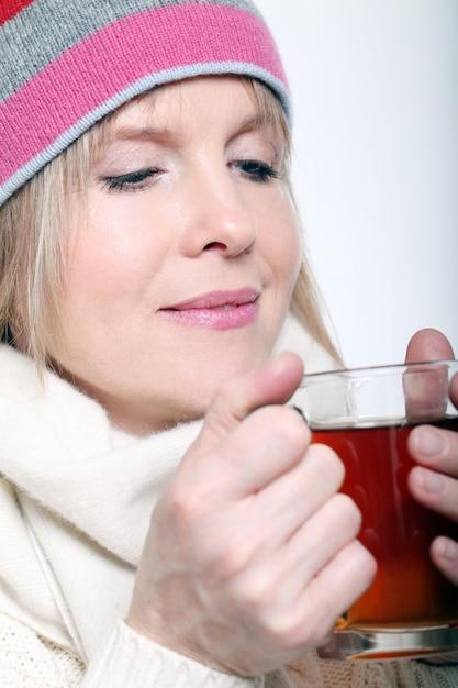 Medio leeftijdsvrouw met hete thee die de winterkleren op een witte achtergrond draagt Gratis Foto