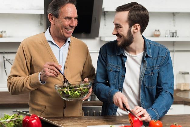Medio schot gelukkige vader en zoon die salade in keuken maken Gratis Foto