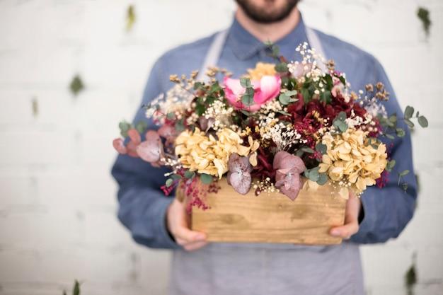 Medio sectie van de mens die houten krat met kleurrijke bloemen houdt Gratis Foto