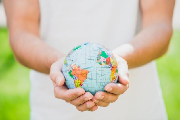 Medio sectie van de mens die kleine bol in de hand houdt Gratis Foto