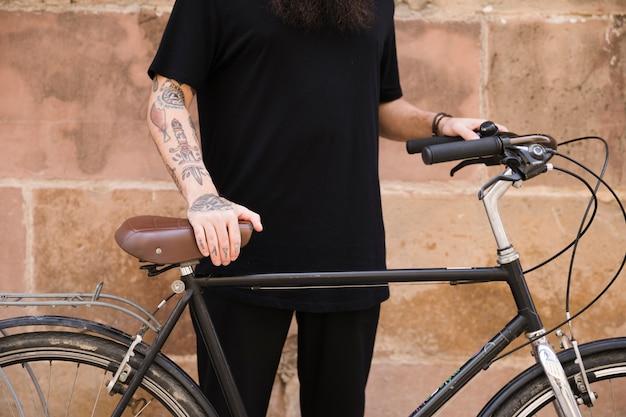 Medio sectie van een mens in zwarte kleding die zich met zijn fiets bevindt Gratis Foto