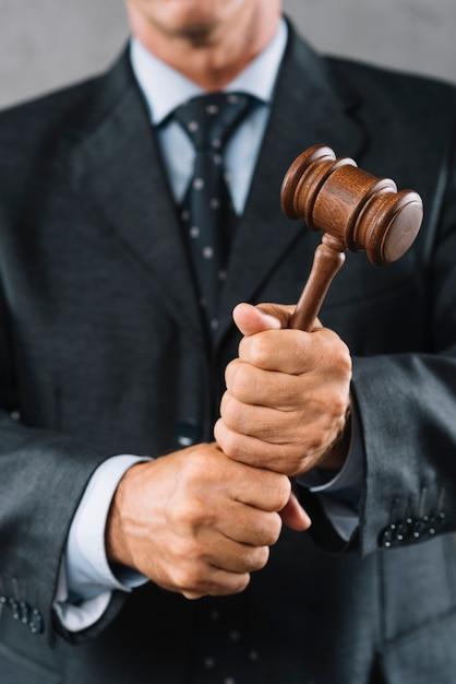 Medio sectie van mannelijke advocaat die houten houten hamer in hand houdt Gratis Foto