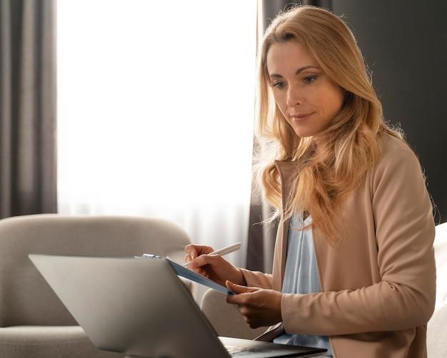 Medio shot therapeut die aantekeningen maakt met laptop op schoot Premium Foto