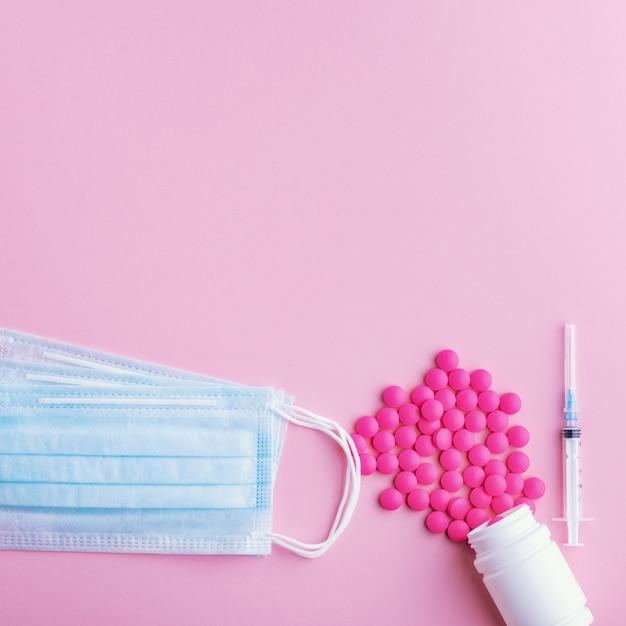 Medisch masker chirurgisch beschermend virus, griep, ziekte, pillen en spuit. geïsoleerd op een roze achtergrond. Premium Foto