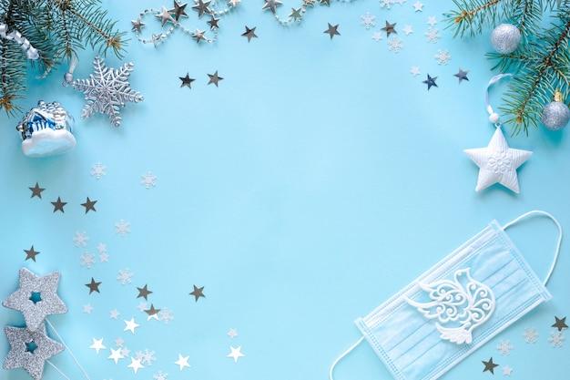 Medisch masker en kerstversiering op blauwe ondergrond Gratis Foto