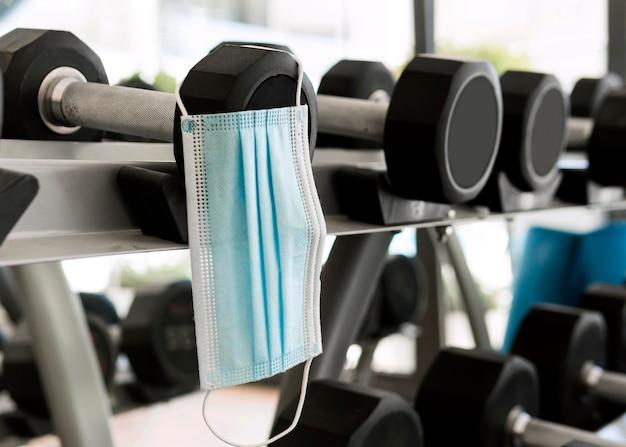 Medisch masker in de sportschool die aan gewichten hangt Gratis Foto