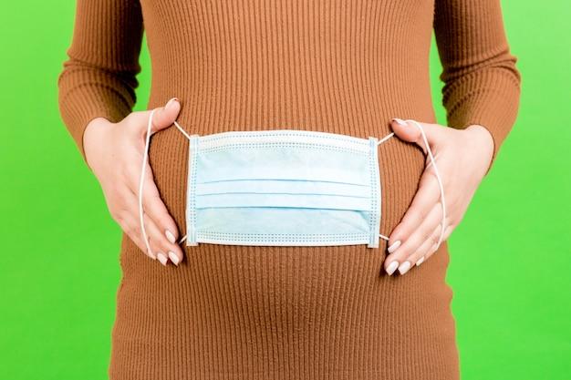 Medisch masker op de buik van een zwangere vrouw, bescherming. concept van virus Premium Foto