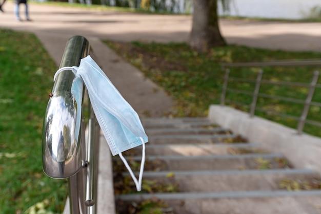 Medisch masker opknoping door trap op reling in stadspark Premium Foto