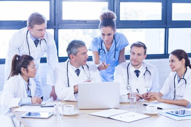 Medisch team dat laptop onderzoekt en een bespreking heeft bij conferentieruimte Premium Foto