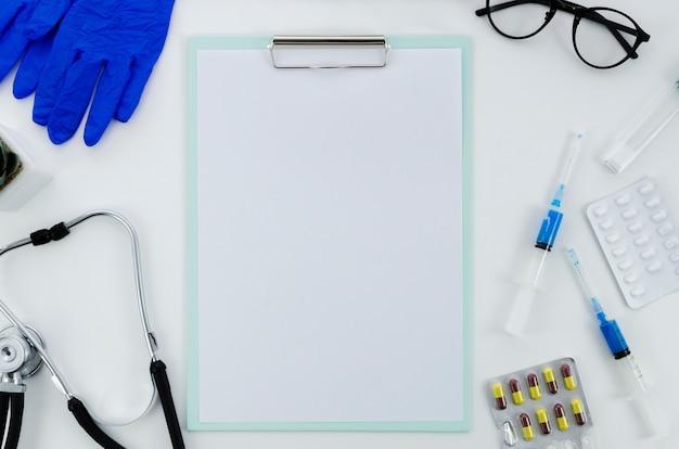 Medische apparatuur met pillen en blanco papier op klembord op witte achtergrond Gratis Foto