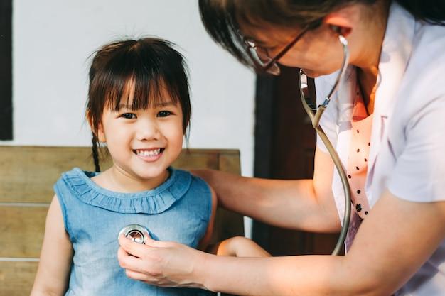 Medische arts die stethoscoop met behulp van die ademhalingsgeluid van jong geitje controleert. ziekte en gezondheid concept. Premium Foto