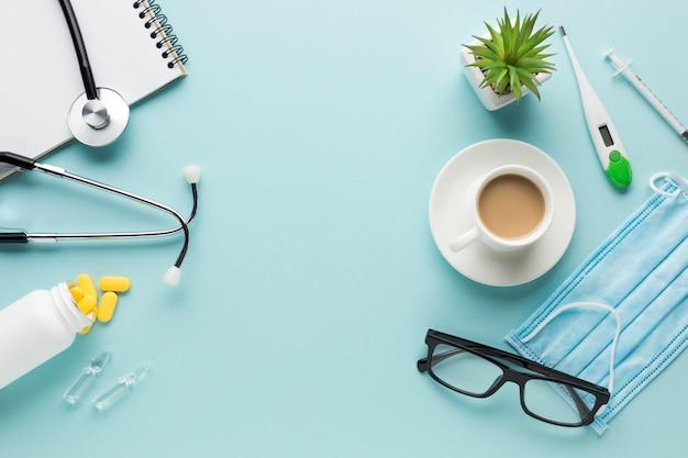 Medische benodigdheden met kopje koffie en vetplant op blauwe achtergrond Gratis Foto