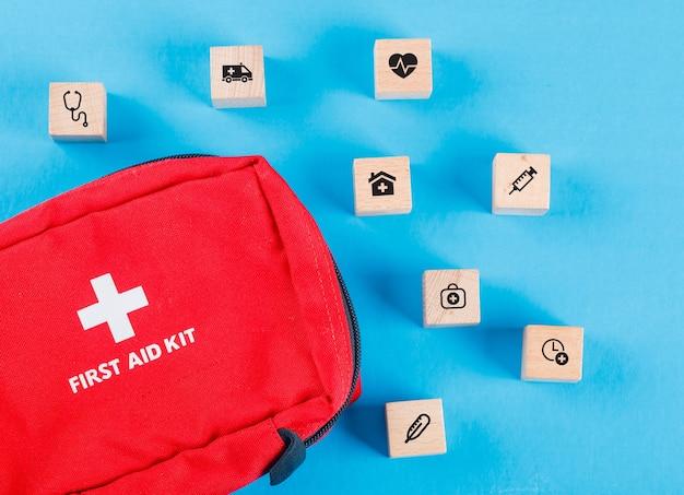 Medische concept met houten blokken met pictogrammen, ehbo-tas op blauwe tafel plat leggen. Gratis Foto