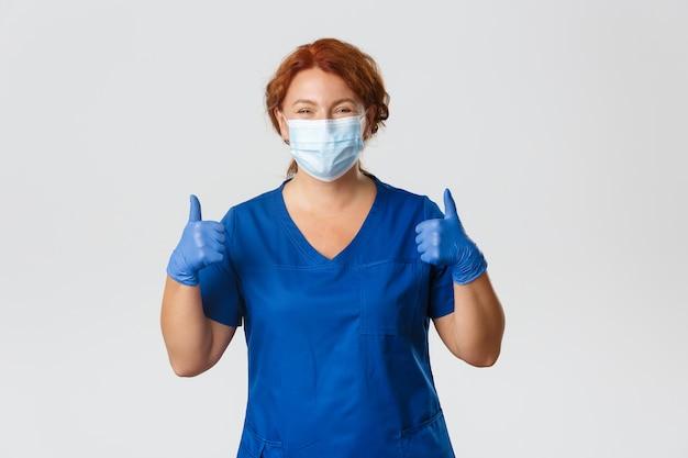 Medische hulpverleners, covid-19 pandemie, coronavirus-concept. gelukkig lachend verpleegster, vrouwelijke arts van middelbare leeftijd in scrubs, medisch masker en handschoenen met thumbs-up in goedkeuring, kliniek aanbevelen. Premium Foto