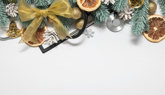 Medische kerstmisachtergrond met stethoscoop, klembord en kerstmisbomen met ballen en klokken Premium Foto