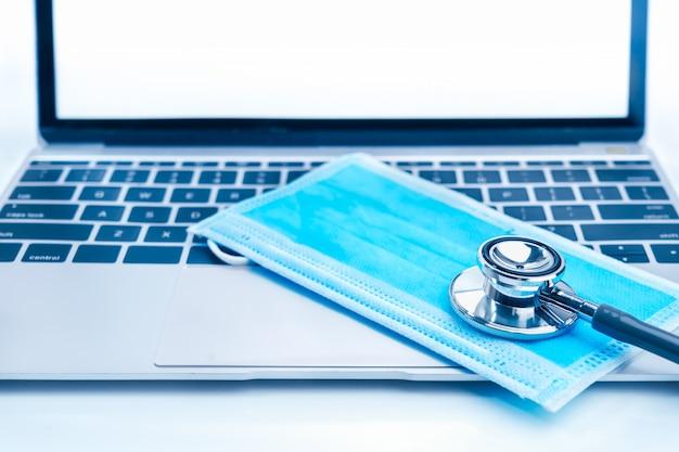 Medische stethoscoop voor artsencontrole op laptop met medische gezichtsmaskers als medisch concept Premium Foto