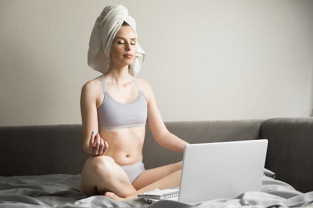 Mediteren met laptop, negatieve emoties in het weekend thuis verlichten, bewuste rustige jonge zakenvrouw of student die ademhalingsyoga-oefeningen op de werkplek beoefent Premium Foto
