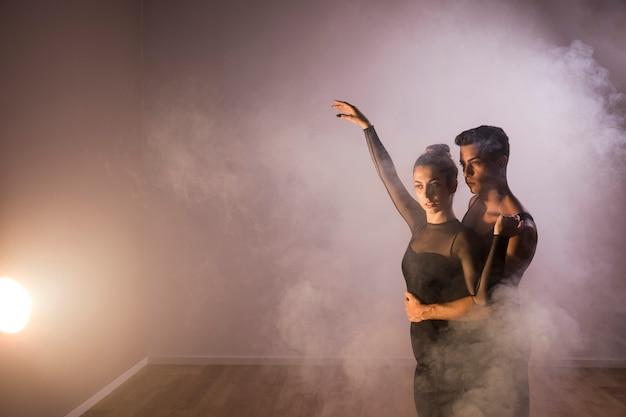 Medium geschoten dansers koppelen elkaar in rook Gratis Foto