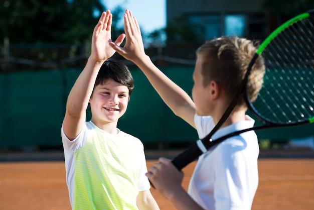 Medium geschoten gelukkige kinderen hoog fiving Gratis Foto
