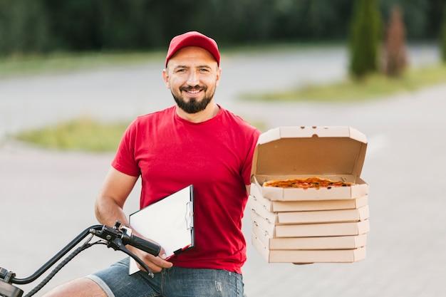 Medium geschoten kerel die pizzadozen en klembord houdt Gratis Foto