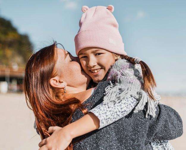 Medium geschoten moeder die klein meisje vasthoudt Gratis Foto