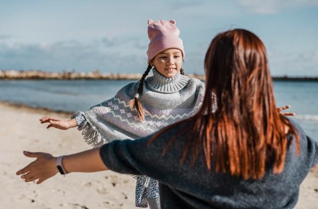 Medium geschoten moeder en dochter op het strand Gratis Foto