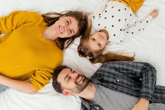 Medium geschoten ouders en kind in bed bovenaanzicht Gratis Foto