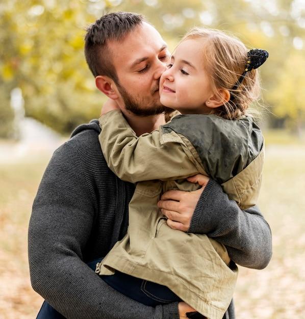 Medium geschoten vader die meisje op wang kust Premium Foto