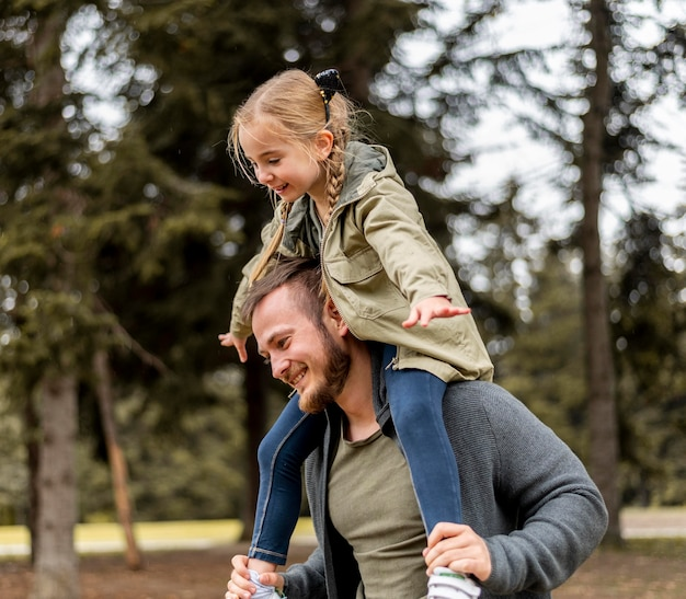 Medium geschoten vader met meisje op schouders Premium Foto