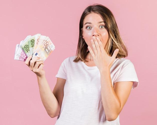 Medium geschoten verrast meisje bedrijf geld Gratis Foto