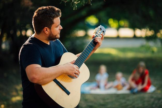 Medium schoot zijdelings vader gitaar te spelen Gratis Foto
