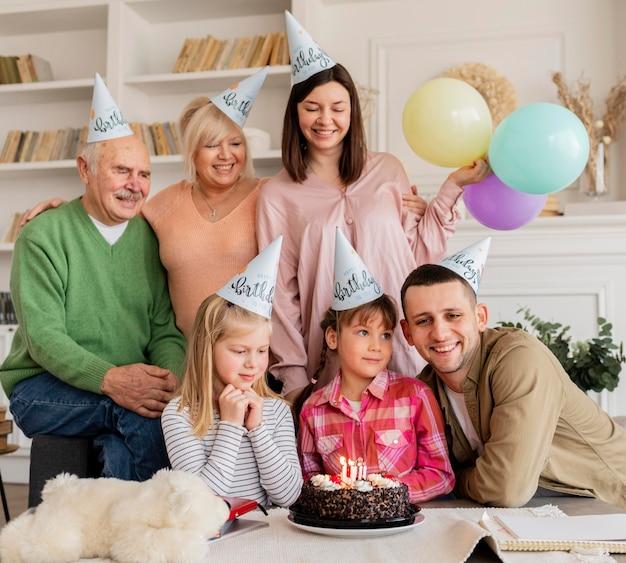 Medium shot gelukkig gezin met feestmutsen Gratis Foto
