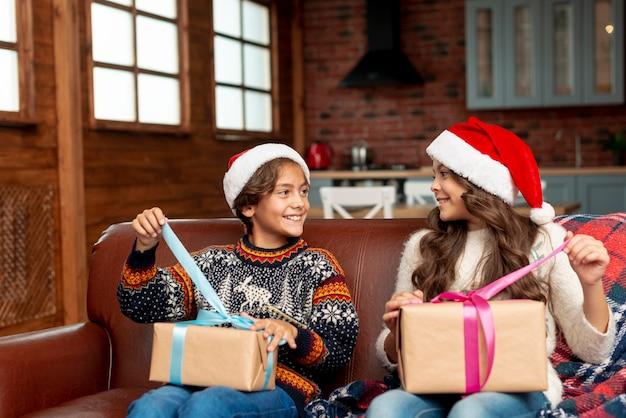 Medium shot gelukkige broer en zus geschenken openen Gratis Foto