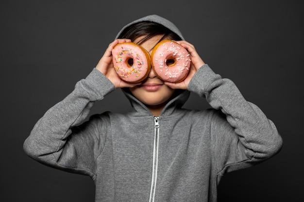 Medium shot jongen met donuts Gratis Foto