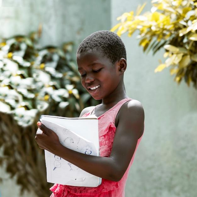 Medium shot jongen met notitieboekje Gratis Foto