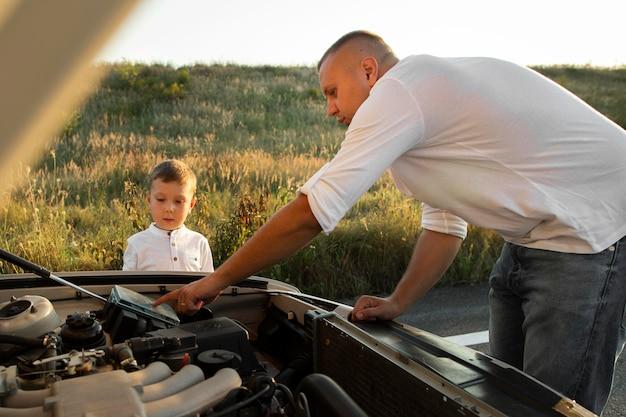 Medium shot man die kind leert over auto Gratis Foto