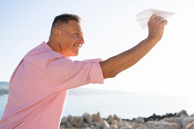 Medium shot man met papieren vliegtuigje Gratis Foto