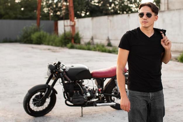 Medium shot man poseren in de buurt van motorfiets Gratis Foto