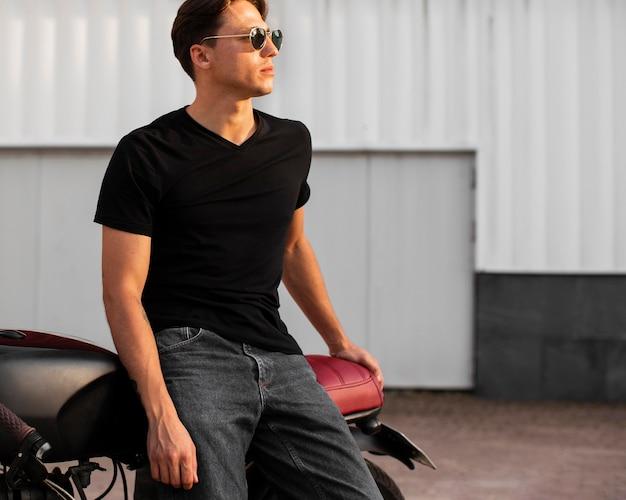 Medium shot man poseren met motorfiets Gratis Foto
